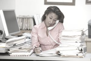 A busy office worker on phone with stacks of paperwork