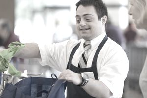 Man with Down Syndrome working at a grocery store and greeting a customer while bagging