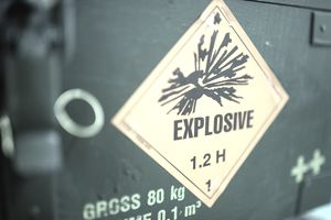 A warning sign reading 'Explosive' sits on a case of artillery munitions