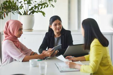 Female professionals discussing paperwork and using digital tablet and laptop at a conference table