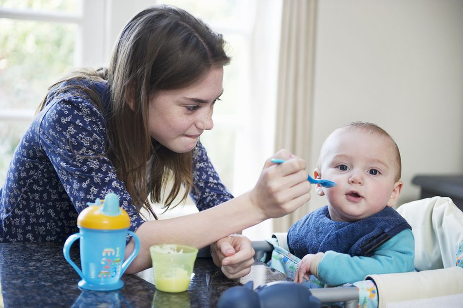 Girl feeding baby brother at table
