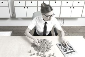 Woman counting change with an oversized calculator