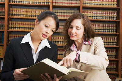 business women looking at library reference book