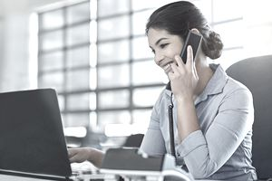 Young businesswoman talking on the phone while using a laptop at work