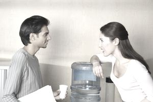 Man and woman chatting by water cooler