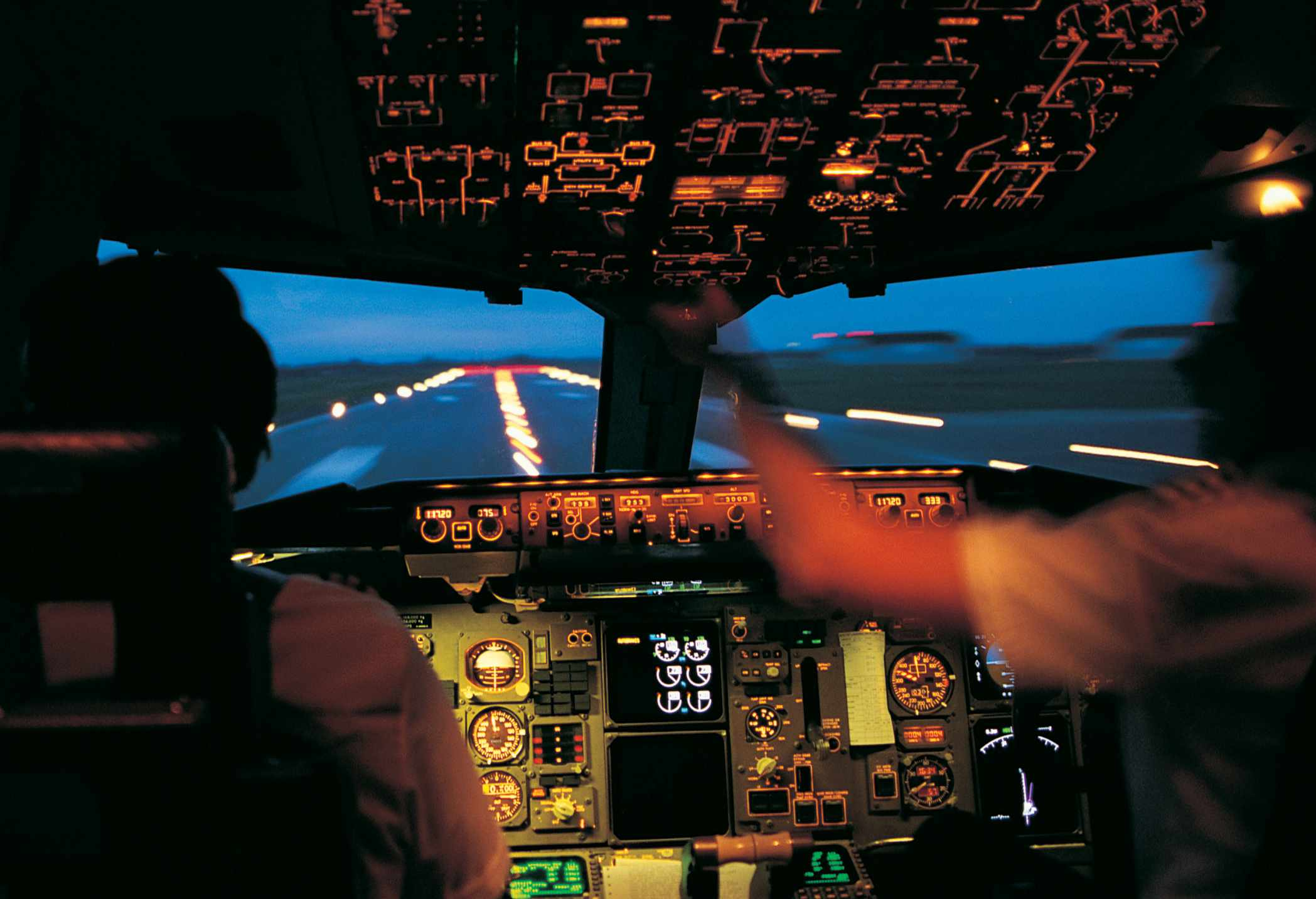 Pilot and copilot in the cockpit during a night flight.