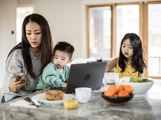 Woman multitasking at home, working and caregiving