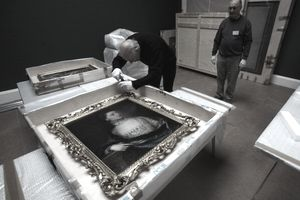 Museum staff unpack a painting from shipping packaging