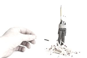 Hand setting fire to a doll dressed as a businessman tied to a stake, representing the concept of manager retaliation.