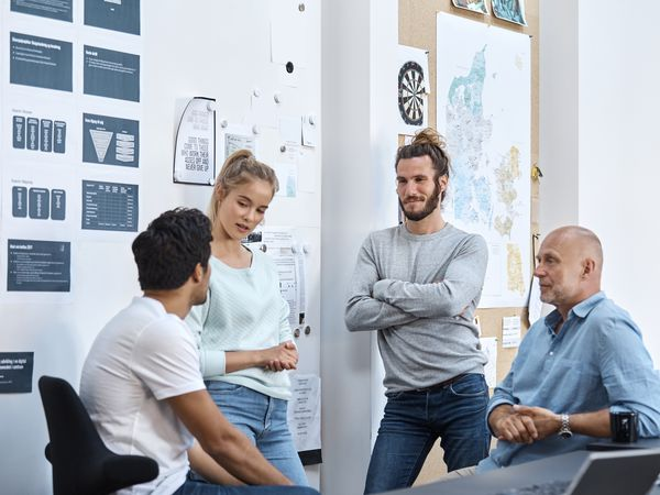 Four employees, a woman and three men, dressed in blue, denim, white and gray talk with each other in a workplace that has adopted a casual dress code.