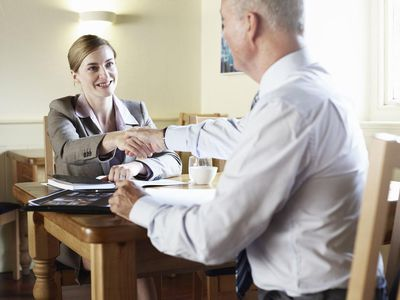 Business people shaking hands in cafe