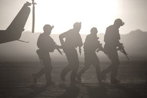 Silhouette of soldiers near helicopter in desert landscape
