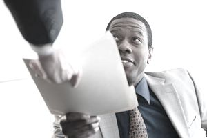 African American man dressed in suit being handed his executive job offer in a folder