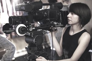 Young woman on set operating a film camera.
