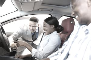 salesman showing new car to a couple