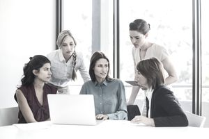 A manager provides direction and communication with her staff as they gather around a laptop.