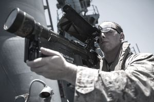 a soldier holding a weapon and looking into its scope