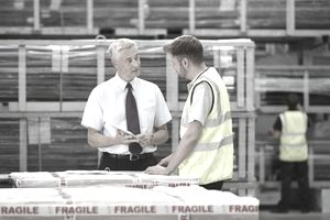 Warehouse worker and manager discussing the worker's performance in the warehouse.