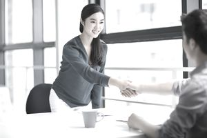 A young woman shaking hands after interviewing at a temporary work agency.