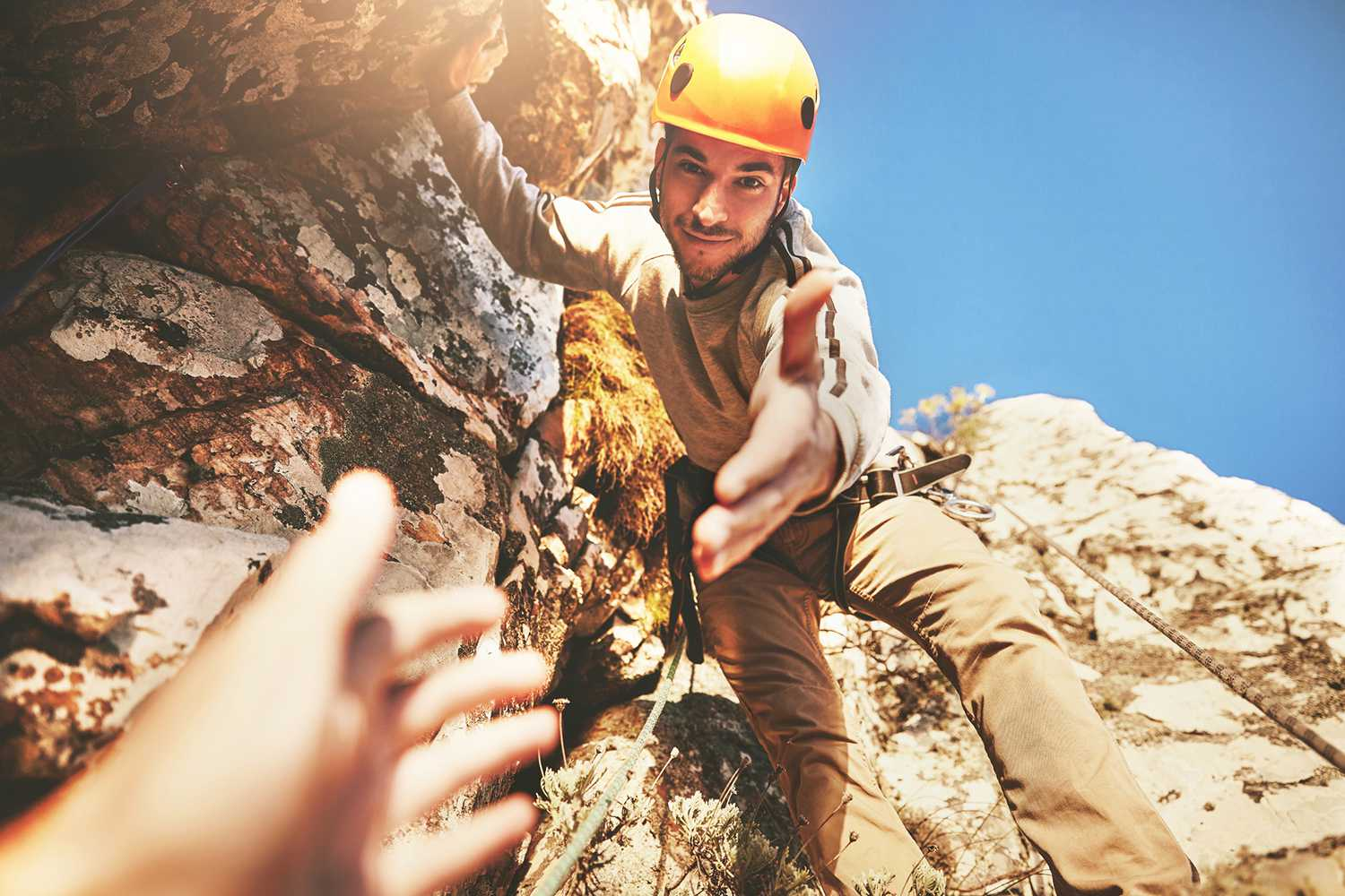 Personal perspective reaching for hand of rock climber