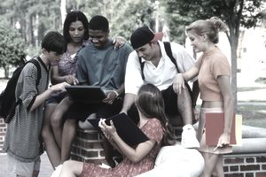 group of teens looking at a tablet