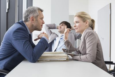Colleagues having a positive disagreement discussion in the office, smiling.