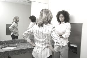 Two women standing by sink in bathroom, talking
