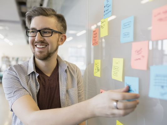 Smiling businessman arranging sticky notes on whiteboard