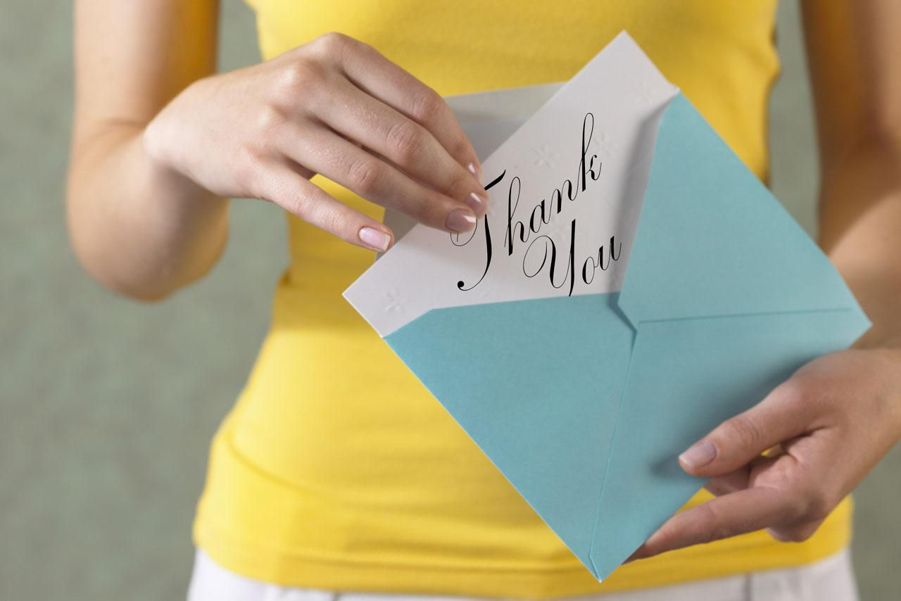 Person putting a follow-up thank you card into an envelop after an interview.