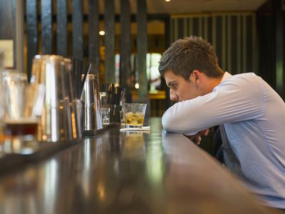 Lonely businessman sitting at bar after being laid off