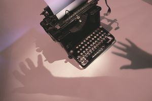 ghostly shadow hands near old typewriter