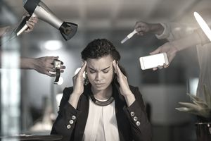 Woman trying to concentrate at her desk while hands hold distracting items around her head.