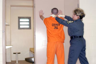 Corrections officer searching a jail inmate