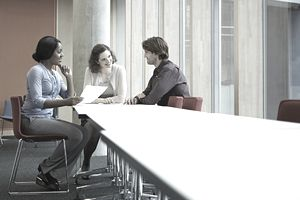 Three colleagues discussing in meeting room