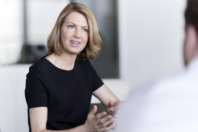 Businesswoman gesturing and talking to businessman