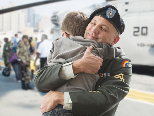 A soldier returning home and hugging his son
