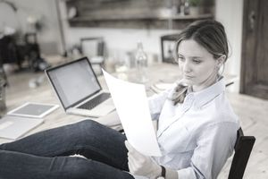 Woman sitting at desk at home with feet up reading a script