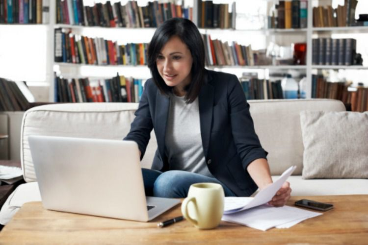 Woman holding papers and working on a laptop