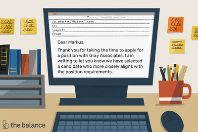 Image shows a computer on an office desk. Text in the email reads