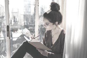 Young woman writing in diary.