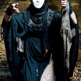 A masked woman seems to be rising from a grave.