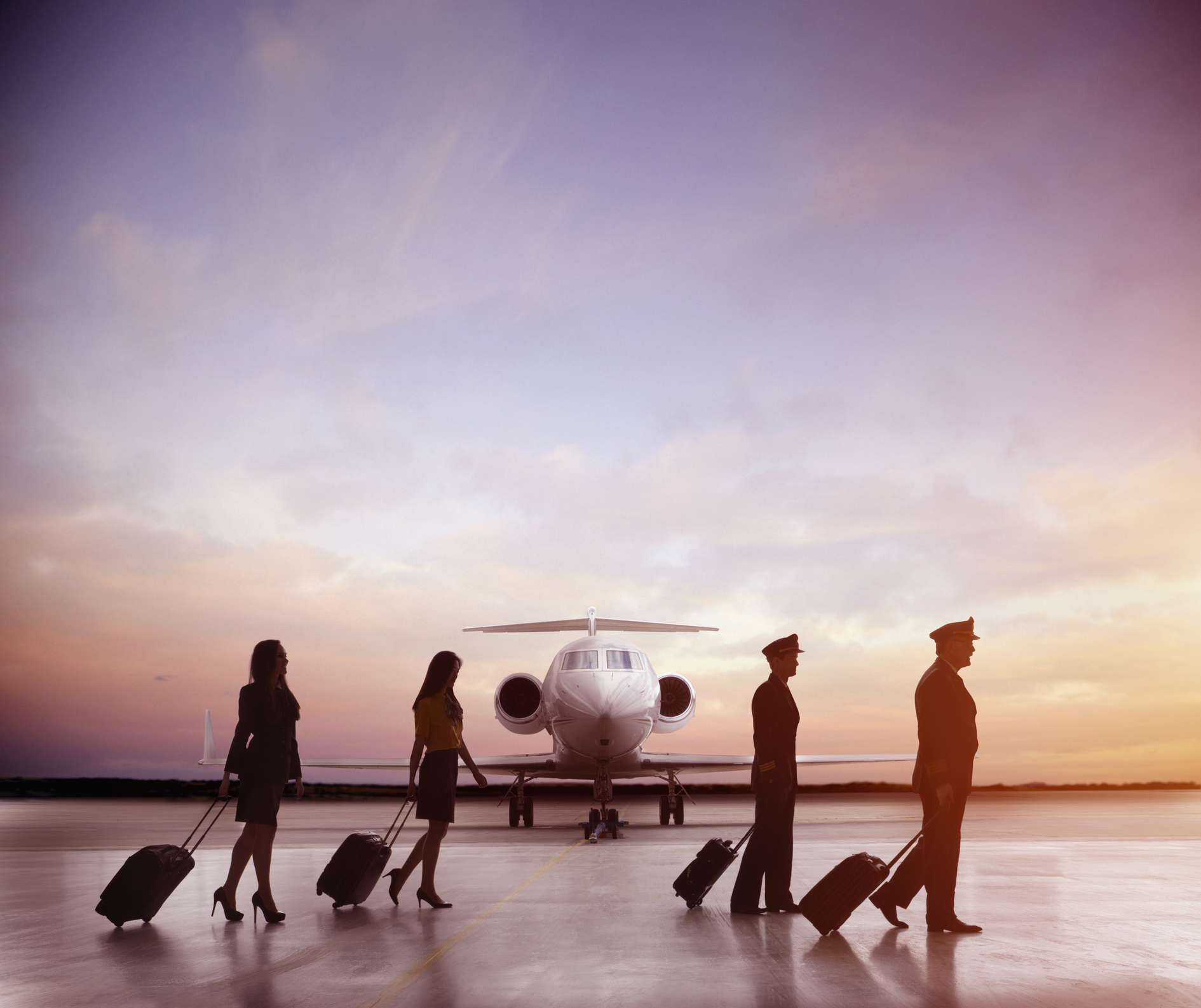 Pilots and flight attendants walking on airport runway in front of a jet.