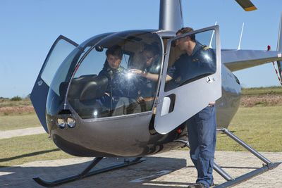 Flight instructor showing student pilots flight deck of helicopter