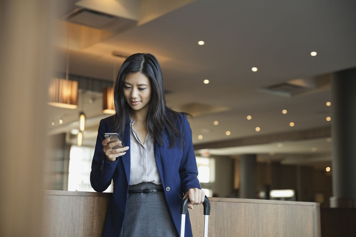 Lawyer using smart phone in hotel lobby