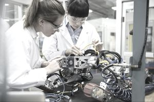 Two workers assembling a robot in a factory