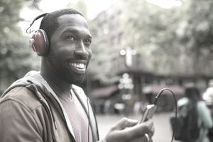 Smiling man with headphones listening to music with smart phone