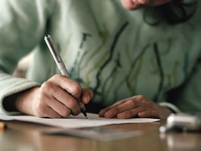 Close up of a person handwriting a letter on paper.