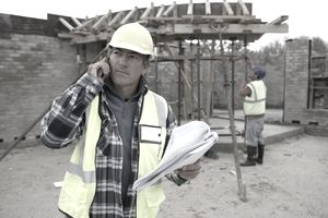 A construction manager using his phone at a construction site