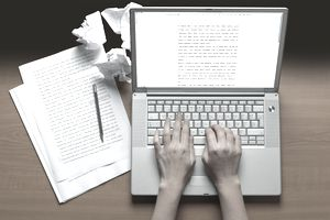 hands typing on a laptop next to printouts and crumbled pieces of paper