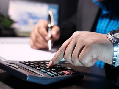 Man using a calculator to figure out his take home pay amount.